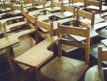 Старые деревянные стулья в школе, винтажные стулья лекции стоковое фото