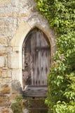 Старые, деревенские деревянные двери в каменном доме с взбираясь плющом Стоковое Изображение