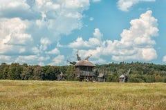 Старые деревянные ветрянки на поле Стоковые Фото