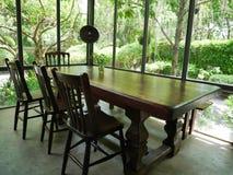 Старые естественные деревянный стол и стулья в винтажном стиле внутри стеклянного дома Стоковые Фото