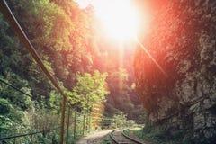 Старые железная дорога или железная дорога среди гор и зеленых деревьев в лете захода солнца освещают Стоковые Изображения