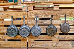 Старые железные баки и античные сковороды висят на крюках утвари кухни старые Стоковое Фото