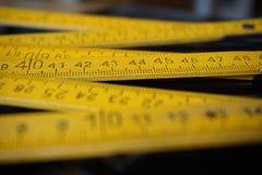 Старые желтые складывая сантиметры правителя метра измеряя стоковая фотография