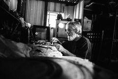 Старые задумчивые посадочные места человека в сарае делая гончарню глины Стоковые Изображения RF