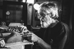 Старые задумчивые посадочные места человека в сарае делая гончарню глины Стоковое Фото