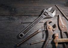 Старые инструменты locksmith на сером цвете и треснутой деревянной предпосылке Стоковые Фото