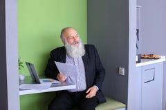 Старые директор или заведущая бизнесмена высчитывают минимальное balanc Стоковое Фото