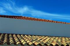 Старые и новые черепицы глины на небе предпосылки голубом стоковое изображение