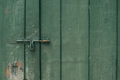 Старые и ржавые защелка и замок двери на зеленой деревянной двери Темный тон стоковое фото rf