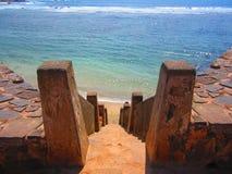 Старые каменные лестницы к пляжу с волнами моря стоковая фотография