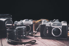Старые камеры фильма с объективами и случаи на древесине против черной предпосылки Фокус года сбора винограда тонизированный и се стоковые изображения