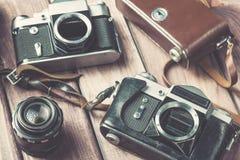 Старые камеры фильма с объективом и случаем на деревянной предпосылке Фокус года сбора винограда тонизированный и селективный Стоковые Фото