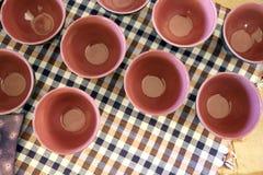 Старые керамические чашки на таблице скатерти Стоковое Фото