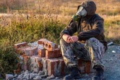 Старые кирпичи от разрушенного здания и человека сидя в маске противогаза на этих кирпичах Стоковые Изображения
