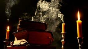 Старые книги на таблице светом горящей свечи акции видеоматериалы