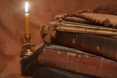 Старые книги светом горящей свечи Стоковые Изображения RF