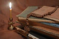 Старые книги светом горящей свечи Стоковые Изображения