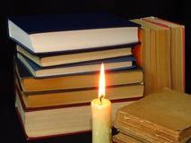 Старые книги штабелированные в куче и горящей свече стоковые изображения rf