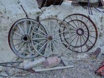 Старые колеса телеги металла выровнялись вверх вдоль горного оборудования в пустыне в Аризоне в дезертированном городке минирован Стоковые Фото