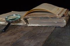 Старые коричневые книга и лупа на деревенской предпосылке r Винтажный тонизировать стоковое фото rf