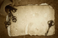 Старые ключи на старой бумажной предпосылке Стоковые Фото