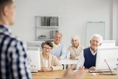 Старые люди слушая к учителю стоковое изображение