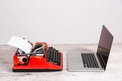 Старые машинка и компьтер-книжка на таблице Концепция прогресса технологии Стоковая Фотография