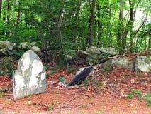 Старые могильные камни в плохом состоянии рядом с колониальной стеной утеса стоковые изображения rf