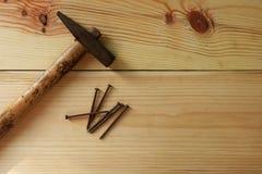 Старые молоток и ноготь на деревянном столе текстуры Стоковое Изображение RF