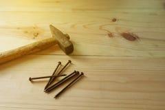 Старые молоток и ноготь на предпосылке текстуры деревянной Стоковая Фотография RF