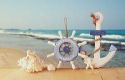 Старые морские деревянные колесо, анкер и раковины на деревянном столе над предпосылкой моря Стоковое фото RF