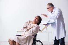 Старые мужские психиатр и пациент доктора в кресло-коляске стоковые изображения