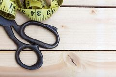 Старые ножницы и портновский метр на деревянной предпосылке стоковые изображения