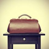 Старые доктора кладут в мешки на таблице, с ретро влиянием фильтра Стоковая Фотография