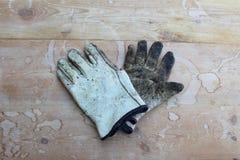 Старые перчатки работы на выдержанной деревянной таблице стоковые изображения