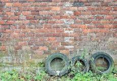 Старые покрышки перед старой кирпичной стеной Стоковые Изображения