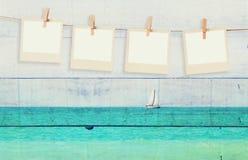 Старые поляроидные рамки фото вися на веревочке с с изображением двойной экспозиции парусника на горизонте на море и деревянном б Стоковое фото RF