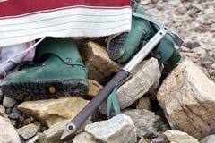 Старые пластичные ботинки горы и ось льда на камне Стоковые Фотографии RF