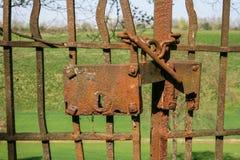 Старые ржавые ворота с зеленым полем на заднем плане стоковое фото rf