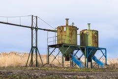 Старые ржавые силосохранилища для еды озером Стоковая Фотография