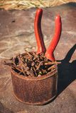 Старые ржавые сломанные инструменты, ногти и плоскогубцы на предпосылке ржавчины Стоковое Фото