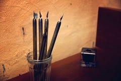 Старые ручки на таблице рядом с чернильницей, трассировки пера помарок на стене Стоковое фото RF