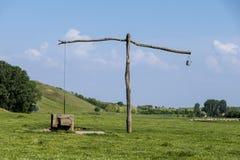 Старые сербские колодец и shadoof стреловидности на зеленом луге Стоковая Фотография