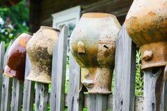 Старые сломанные кувшины глины на деревянной загородке Стоковое Фото