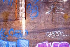 Старые сломленные лестницы к крыше Зима Сосульки висят Кирпичная стена со слезать краску запятнанную с краской для пульверизатора стоковые фото
