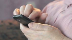 Старые сморщенные руки держа мобильный телефон конец вверх сток-видео