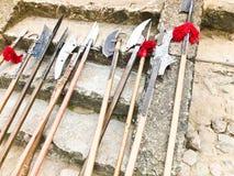 Старые старые средневековые холодные оружия, оси, алебарды, ножи, шпаги с деревянными ручками лижут на каменных шагах замка стоковое изображение rf