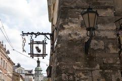 Старые столб и caffe лампы подписывают винтажную каменную стену в Львове Стоковое Изображение