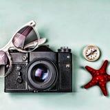 Старые сувениры камеры, компаса и моря на голубой предпосылке Стоковые Фотографии RF