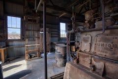 Старые тепловозные стойки генератора бездельничают на город-привидении шахты хищника стоковое изображение